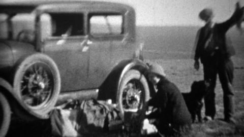 1934: Man holding up hunted dead bird beside model A car Footage