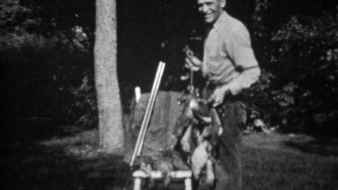1934: Man with stringers of dead hunted birds smiles at dog Live Action