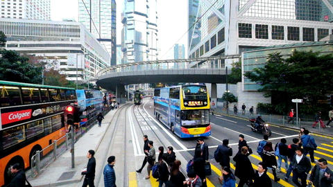 Modern city street view with people moving at crossroad. Hong Kong Footage
