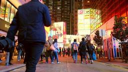 People walking at night city street with illuminated shopping malls. Hong Kong Live Action