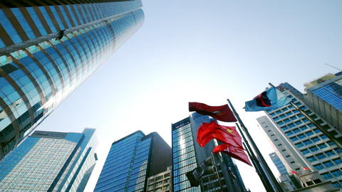 Hong Kong and China waving flags at central city square among modern skyscrapers Footage