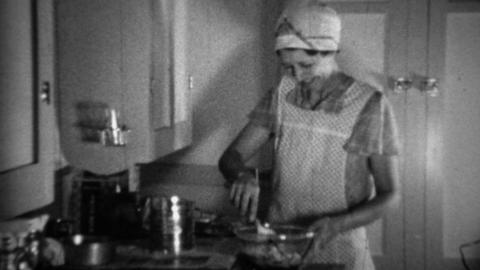 1936: Aproned women cooking in kitchen sifting flour for biscuits Footage