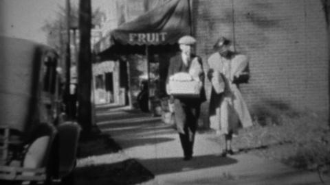 1936: Couple grocery shopping from fruit store walking bags of food Footage