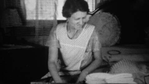1936: Woman packing clothes into suitcase seated in living room Footage