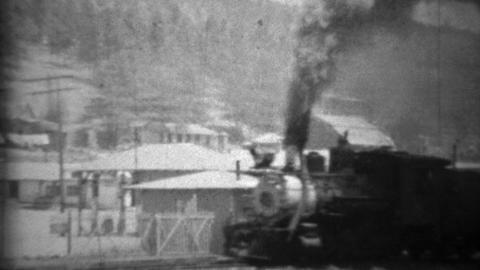 1934: Dirty smoky locomotive train passing small mountain town Footage