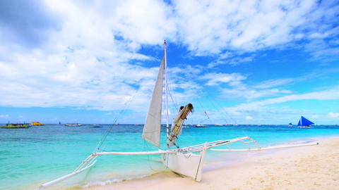 Traditional wooden outriggers sail boat at ocean shore. Boracay, Philippines Footage