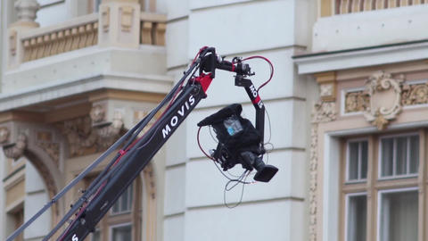 Arm of a crane where is mounted on a professional camcorder moves over a scene 7 Footage