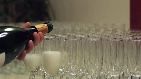 barman pours champagne in glasses placed on the table near the door 57 Footage