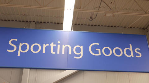 Motion of sporting good sign on sport equipment section inside Walmart store Footage