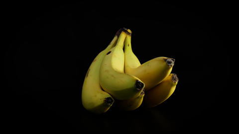 A bunch of yellow bananas slowly rotating against black background Footage