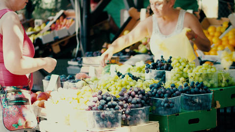 PULA, CROATIA - AUGUST 4, 2017. Woman buying grapes at local marketplace Footage