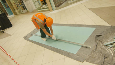 Camera Moves along Builder Cutting Piece in Shopping Mall Footage