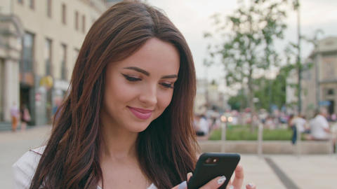 A Beautiful Brunette Using a Mobile Phone Outdoors Footage