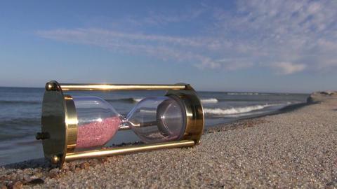 ancient brass sandglass hourglass on sea beach Footage