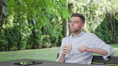 A Young Man Drinking Milkshake in the Park Footage