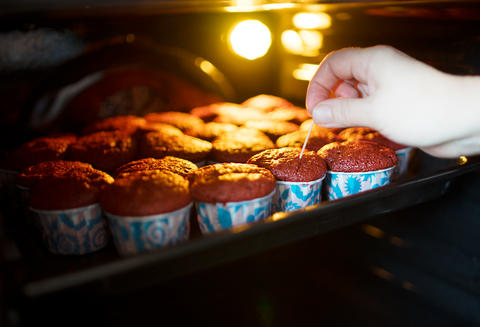 Checking cupcakes for readiness background Photo