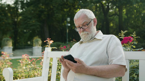 Old Man Using a Phone Outdoors Footage