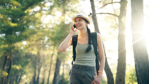 Young tourist girl backpacker in hat chatting with smartphone during walking in Footage