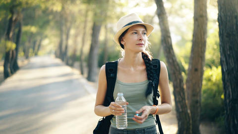 Attractive young touristy girl refreshing by drinkin water after backpacker Live Action