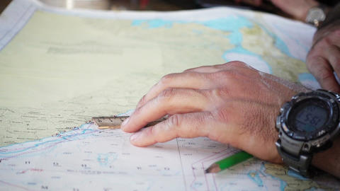 A man chooses a route on the sea map Footage