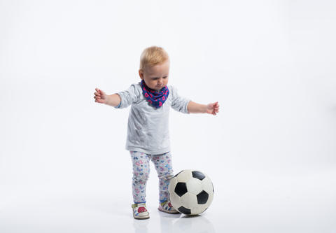 Cute little girl playing with soccer ball. Studio shot Fotografía