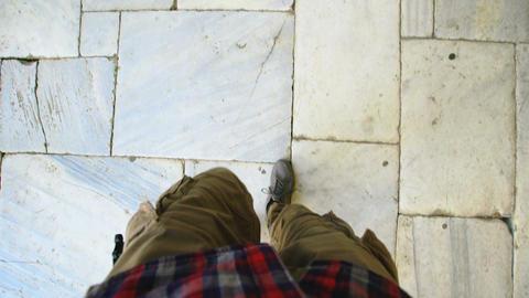 Top view POV of man in sneakers walking historical ancient sidewalk Footage