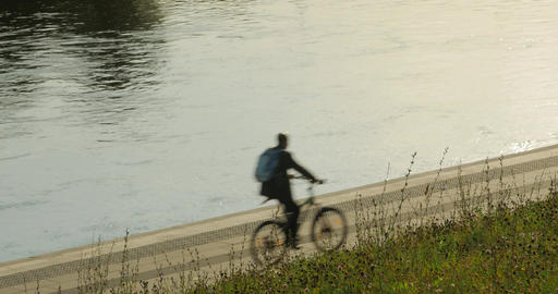 An unidentified cyclist cycles along the riverbank Footage