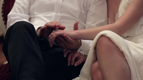 Bride and groom are seated on a chair and holding hands 81 Footage