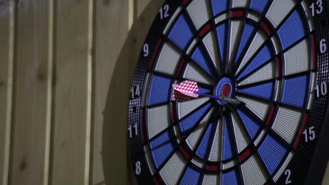 Competitors throw at target with blue and pink arrows 6 Live Action