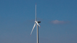 Slow motion seamless loop middle shot white wind turbine blue sky clouds clean Footage