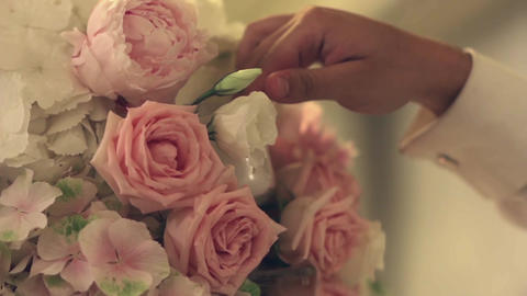 Hand man arranges a candle in a beautiful bouquet of roses located on a meal 29a Footage