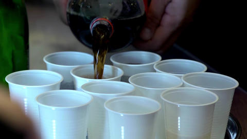 Man poured juice from a glass in white plastic cups placed on a tray 23 Footage