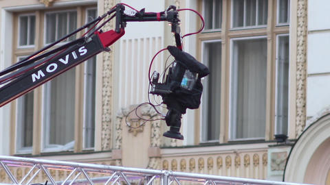 Professional camcorder video located at the head of a crane moves above a stage  Footage