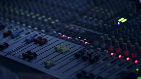 Sound engineer that regulate the sound level from the audio mixer moving buttons Live Action