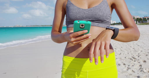 Woman wearing smartwatch touching and swiping screen syncing with smartphone Footage