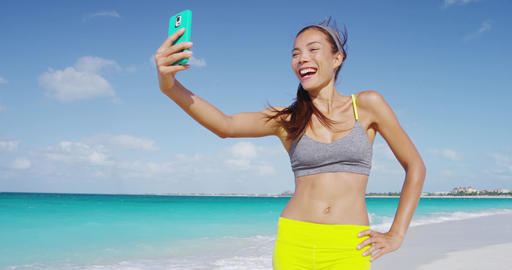 Sporty fresh woman taking selfie with phone laughing after running on beach Live Action