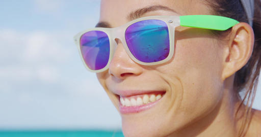 Woman smiling on summer beach wearing sunglasses Footage