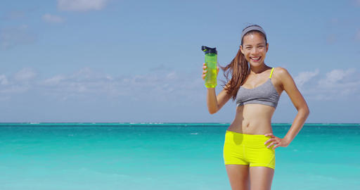 Fitness runner woman drinking water sport bottle showing bottle to camera Live Action