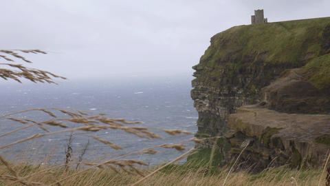 Wind at the Cliffs of Moher with a castle in the background, Ireland Footage