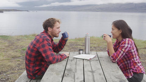 Camping people sitting at table drinking coffee by lake on Iceland Footage