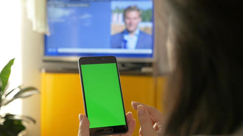 A woman is watching TV, and is holding a smartphone with a green screen. On the Image