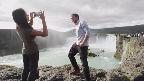 Couple taking photo with smart phone having fun by waterfall Godafoss on Iceland Footage