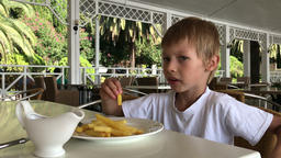 boy eating fast food in a tropical restaurant Image