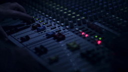 Sound engineer that regulate the sound level from the audio mixer moving buttons Footage