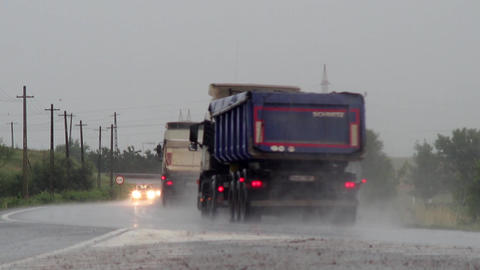 Trucks and small cars running on a wet road because of dense summer rain 77 Footage