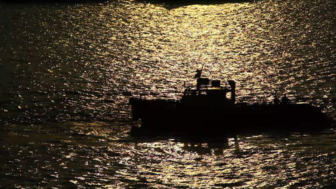Motor boat dark silhouette, move backwards on glossy water ripples Footage