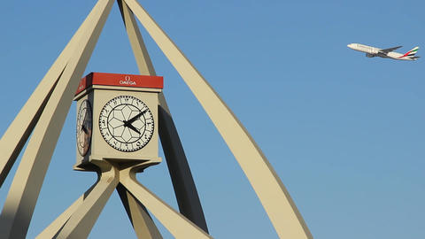 Airliner fly against Dubai Clock Tower, telephoto lens, close view to clock Live Action