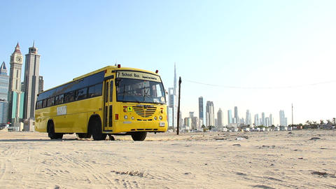 Yellow school bus parked at deserted land, modern tall skyscrapers on background Live Action
