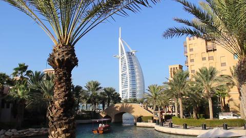 Madinat Jumeirah water channel, small bridge, palm trees and traditional houses Footage