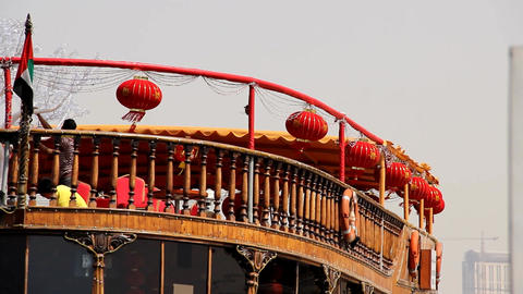 Red chinese paper lantern hang around open top deck of wood dhow boat Live Action